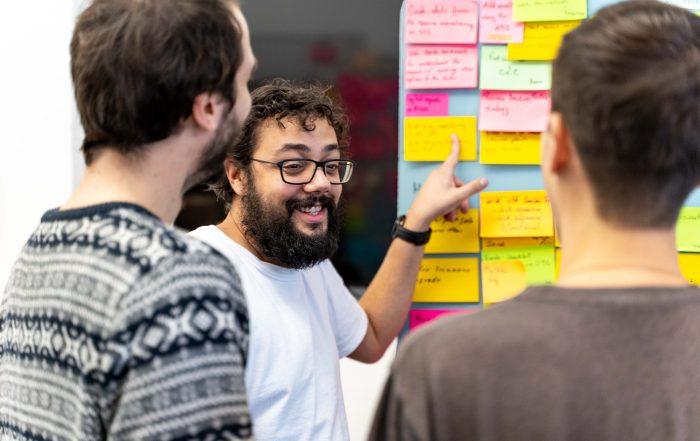 Auf dem Foto sieht man drei unserer Teammitglieder bei einem Scrum-Meeting.